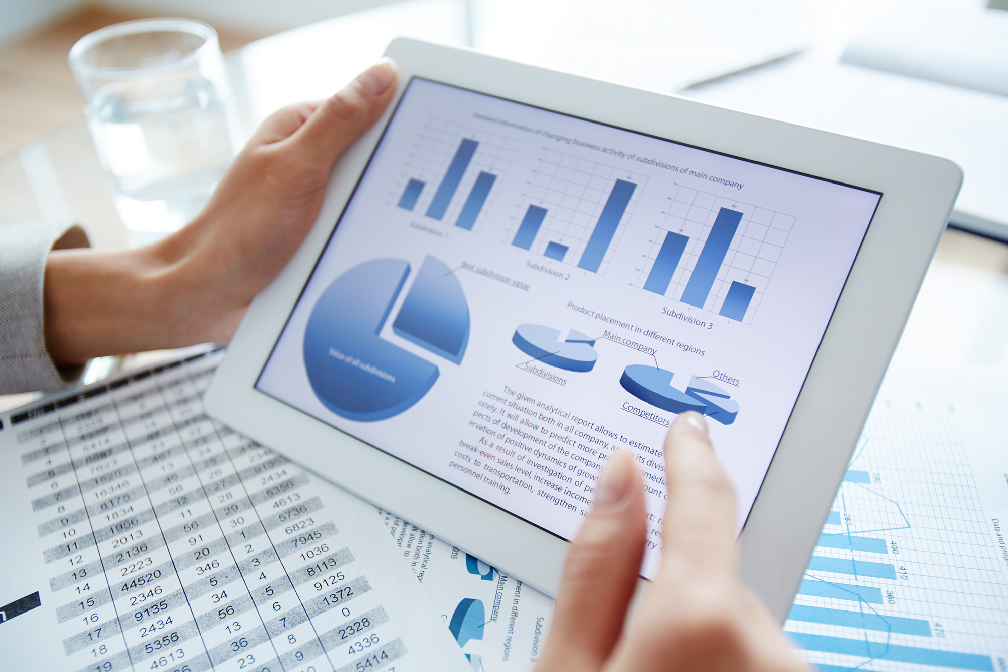 Descriptive image: hands holding a tablet with graphs and charts displayed
